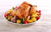 Whole Roast Spicy Chicken With Potatoes, On Plate Over Wooden Background poster