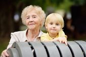Beautiful Granny And Her Little Grandchild Walking Together In Park. Grandma And Grandson Together.  poster