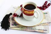 Worry beads and coffee - the Arab businessman's constant companions - on a pile of high denomination