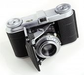 An early 35mm film camera, dating from about 1942, still using bellows technology and the fixed front cell focusing lens. Brand name removed. Isolated on white with a light shadow. poster