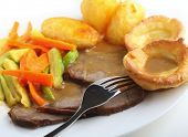 Traditional british meal of roast beef and yorkshire pudding (popovers) served with roasted potatoes