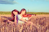 Two Young Women Playing Guitar And Violin Outdoors. Split Toning.