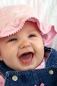 Bebê rindo no chapéu-de-rosa