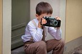 Cute little boy with retro camera outdoors