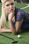 Sexy Blonde Girl Pays Golf Lyng With Golf-club And Ball