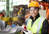 stock photo of assembly line  - Portrait of young engineer taking notes in factory - JPG
