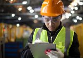stock photo of workplace safety  - industrial engineer writing on notepad in factory - JPG