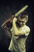 stock photo of gory  - Mad maniac with bloody chainsaw over grunge background - JPG