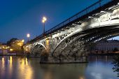 SEVILLE, SPAIN - MAY 15: The Isabel II bridge of Seville, also known as the Triana Bridge, in early evening on May 16, 2013 in Seville, Spain. Built in 1847-1852, it is the oldest bridge in Seville.