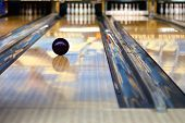 stock photo of indoor games  - Swirling bowling ball is rolling down the path to the bowling pins - JPG