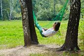 Young woman lies in hammock suspended between two thick birches