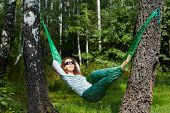 Young smiling woman in dark sunglasses lies in hammock, turning his face to the sun and putting her