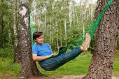 foto of birchwood  - Young barefooted man in glasses with reclines in hammock at birchwood and works on notebook - JPG