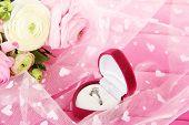 Ranunculus (Perzisch boterbloemen) en verlovingsring, op roze doek