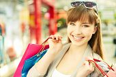 Pretty young shopper with shopping bags smiling at camera