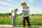 stock photo of spray can  - A preschool aged boy watering the feet of his baby brother with a tine watering can - JPG