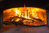 stock photo of oven  - traditional Italian pizza wood oven with raw pizza and large fire in the background - JPG