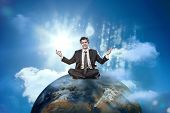 Happy businessman sitting cross legged on top of the world