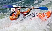 image of rough-water  - an active male kayaker rolling and surfing in rough water