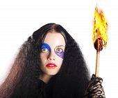 image of facial piercings  - Bizarre woman with piercing stare and facial makeup holding a burning fire torch - JPG