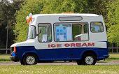 stock photo of ice-cream truck  - Side view of ice cream van in green countryside - JPG
