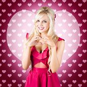 image of heartfelt  - Pretty blonde girlfriend gesturing heartfelt feeling of romance with hands - JPG