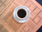 stock photo of nyse  - Coffe cup above a spanish financial newspaper - JPG