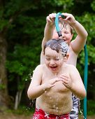 Children playing with water hose outdoors during summer or spring to cool off in hot weather