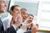 stock photo of excite  - Group of cheerful businesspeople sitting in a row on a presentation and clapping - JPG