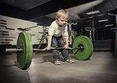 foto of attitude boy  - Determined young boy trying to lift a heavy weight bar - JPG