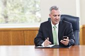 Businessman reading text messages on his phone