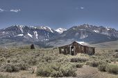 stock photo of wooden shack  - old wooden cabin in the mountains in spring - JPG