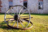 pic of wagon wheel  - Antique wagon wheel lying in the grass in front of a historical building. Fayette State Historical Park. Fayette, Michigan.