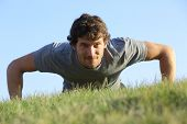 Close Up Of A Man Doing Pushups On The Grass