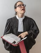 stock photo of toga  - thirty something brunette woman wearing a canadian lawyer toga with a red criminal law book in hand - JPG