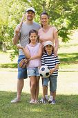 Full length portrait a family of four holding baseball bat and ball in the park
