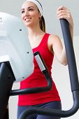 image of elliptical  - Portrait of young woman with elliptic machine in the gym