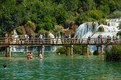 KRKA NATIONAL PARK, CROATIA - JUL 28: Tourists swimming, taking photos and walking on July 28, 2012 on Krka National Park, Croatia. One of most famous Croatian tourist attraction.