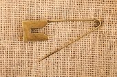 stock photo of brooch  - Vintage brooch or safety pin on jute background - JPG