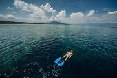 Woman snorkeling in a tropical sea by reef's drop off. Indonesia