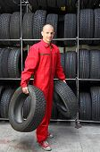 A smiling mechanic in a garage  carrying two tires.