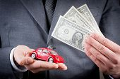Toy Car And Dollars In The Hands Of Business Man Concept For Insurance, Buying, Renting, Fuel Or Ser