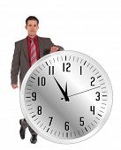 A handsome businessman standing next to a huge clock that shows the eleventh hour. All on white back