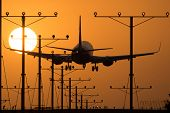 stock photo of lax  - Landing lights during sunset in nature with beautiful orange sky 