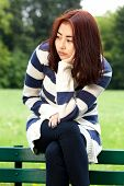 foto of mongolian  - Sad mongolian woman sitting in the park - JPG