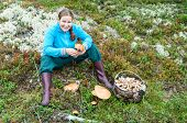 Young Woman Sitting On Moss With Basket Full Mushrooms