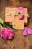 Box with a gift and a peony flower