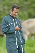 Farmer with overall sending message with smartphone