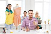 education, fashion and office concept - smiling male drawing sketches and female adjusting dress on mannequin in office and showing thumbsup