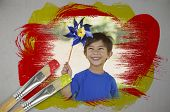 Composite image of little boy with pinwheel with paintbrush dipped in yellow against digitally gener